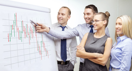 business, money and office concept - smiling business team with forex chart on flip board having discussion photo