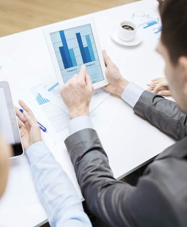 business and office concept - close up of business team with graph on tablet pc screen and coffee in office photo