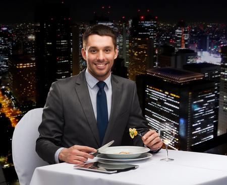 restaurant, people, technology and holiday concept - smiling man with tablet pc eating main course at restaurant photo