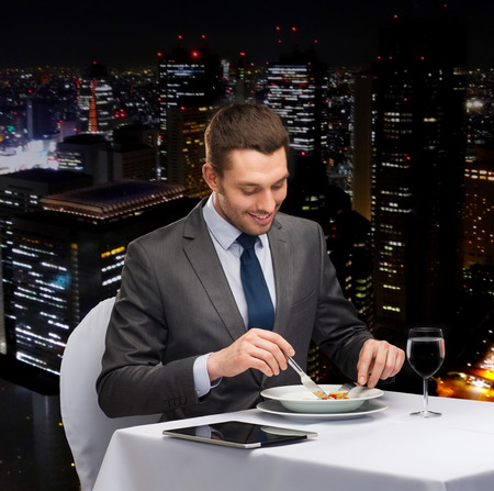 reviewer: restaurant, people, technology and holiday concept - smiling man with tablet pc eating main course at restaurant Stock Photo