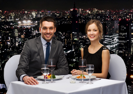 holiday food: restaurant, couple and holiday concept - smiling couple eating main course with red wine at restaurant
