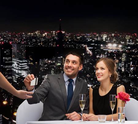 restaurant, couple and holiday concept - smiling couple paying for dinner with credit card at restaurant photo
