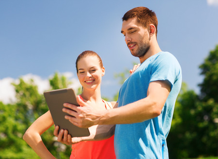 computer classes: fitness, sport, friendship, technology and lifestyle concept - smiling couple with tablet pc computer outdoors
