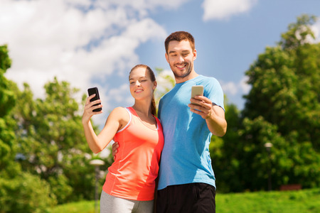 fitness, sport, training, technology and lifestyle concept - two smiling people with smartphones outdoors photo