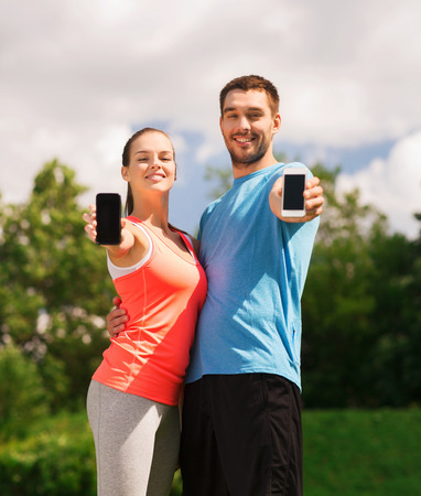 young add: fitness, sport, training, technology and lifestyle concept - two smiling people with smartphones outdoors
