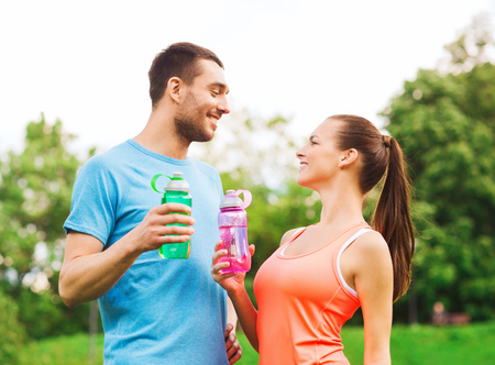 couple exercising: fitness, sport, friendship and lifestyle concept - smiling couple with bottles of water outdoors