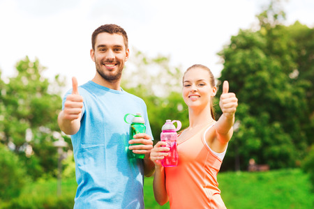 couple exercising: fitness, sport, friendship and lifestyle concept - smiling couple with bottles of water showing thumbs up outdoors