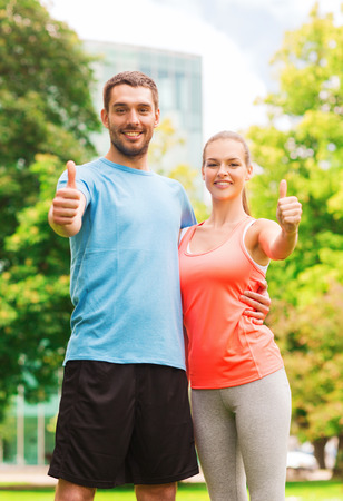 approvement: fitness, sport, friendship and lifestyle concept - smiling couple outdoors showing thumbs up Stock Photo