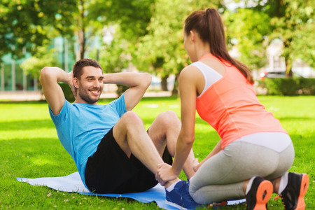 couple exercising: fitness, sport, training, teamwork and lifestyle concept - smiling man with personal trainer doing exercises on mat outdoors