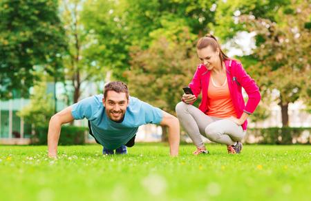 hombres haciendo ejercicio: fitness, deporte, capacitación, tecnología y estilo de vida concepto - hombre sonriente con el entrenador personal de hacer ejercicio al aire libre Foto de archivo