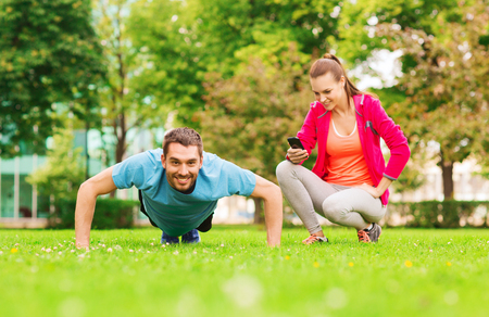 fitness, sport, training, technology and lifestyle concept - smiling man with personal trainer doing exercise outdoors photo