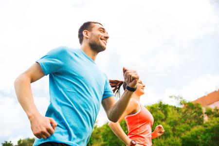 motion: fitness, sport, vänskap och livsstilskoncept - leende par körs utomhus Stockfoto