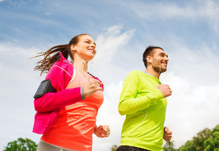 fitness, sport, friendship and lifestyle concept - smiling couple with earphones running outdoors Banco de Imagens
