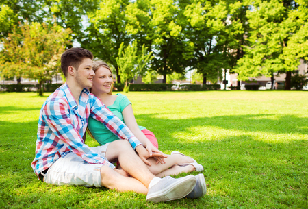 holidays, vacation, love and friendship concept - smiling couple in park photo