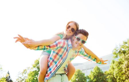 holidays, vacation, love and friendship concept - smiling couple having fun in park Stock Photo