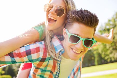 休日、休暇、愛と友情のコンセプト - 笑顔のカップル公園で楽しんで