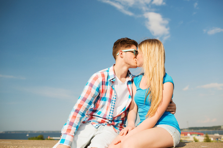 holidays, vacation, love and friendship concept - smiling couple kissing outdoors photo