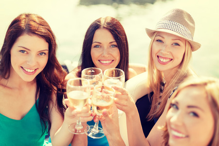 sightseeing: summer holidays, vacation and celebration concept - smiling girls with champagne glasses Stock Photo