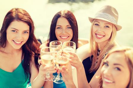Touring: wakacje, wakacje i uroczystości pojęcie - uśmiechnięte dziewczyny z kieliszkami do szampana