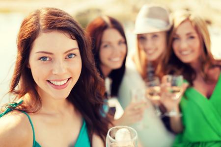 despedida de soltera: vacaciones de verano, vacaciones y celebre concepto - niñas sonriendo con vasos de champán