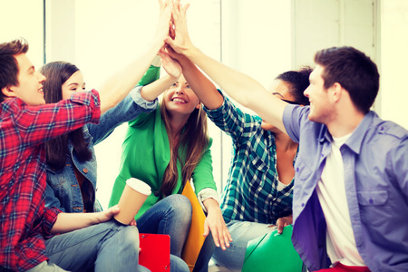 high class: education concept - students giving high five at school