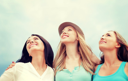 people travelling: summer holidays and vacation concept - girls looking up in the sky Stock Photo