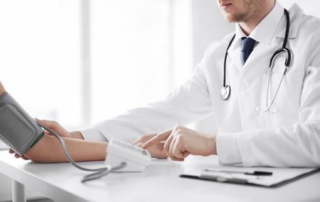 gezondheidszorg, het ziekenhuis en de geneeskunde concept - arts en patiënt meten van de bloeddruk