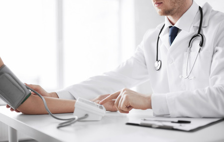 hypotension: healthcare, hospital and medicine concept - doctor and patient measuring blood pressure Stock Photo
