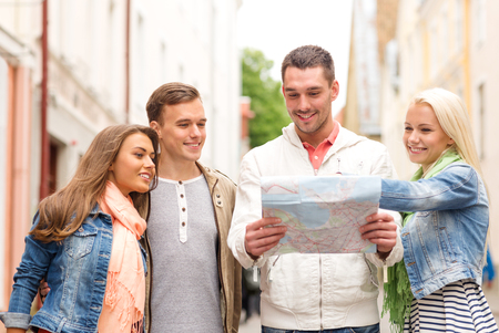 lost city: travel, vacation and friendship concept - group of smiling friends with city map exploring city Stock Photo