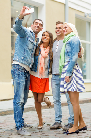 travel, vacation, technology and friendship concept - group of smiling friends making selfie with smartphone camera outdoors photo