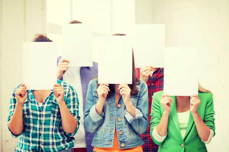 blank papers: education concept - group of students covering faces with blank papers