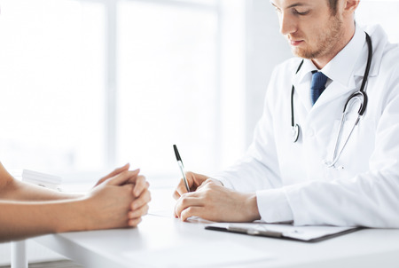prescribing: close up of patient and doctor taking notes Stock Photo
