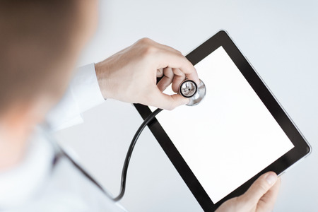 close up of male doctor with stethoscope and tablet pc photo