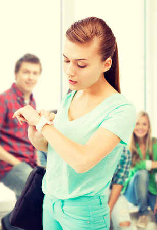 girl with a wristwatch: education and time management concept - student girl looking at wristwatch Stock Photo