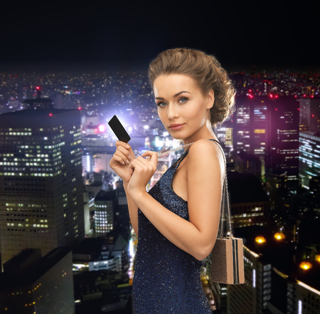 party, celebration, holiday and banking concept - beautiful woman in evening dress with small bag and vip card photo