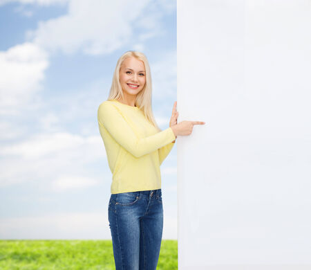 sweater girl: people, advertisement and sale concept - happy woman in sweater pointing finger to blank white board Stock Photo