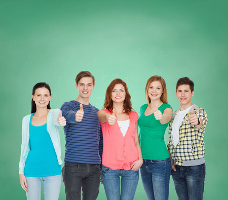 education and people concept - group of smiling students standing and showing thumbs up photo