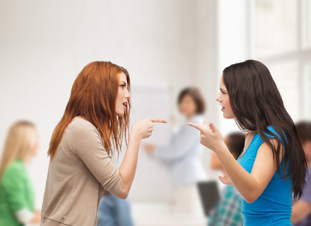 bullying, education, friendship and people concept - two teenagers having a fight at school photo
