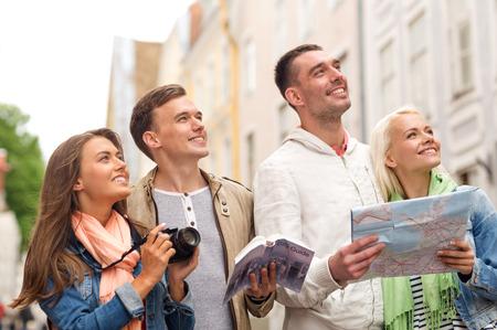 旅行、休暇、技術および友情の概念 - 都市ガイド、photocamera 散策マップと笑みを浮かべてお友達のグループ