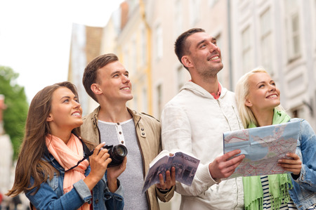 photocamera: travel, vacation, technology and friendship concept - group of smiling friends with city guide, photocamera and map exploring city