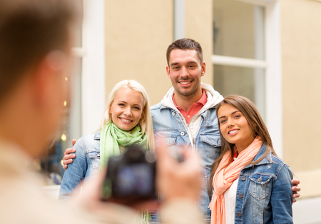 travel, vacation, technology and friendship concept - guy picturing group of friends in city photo