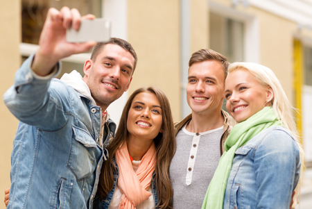 boy friend: travel, vacation, technology and friendship concept - group of smiling friends making selfie with smartphone camera outdoors