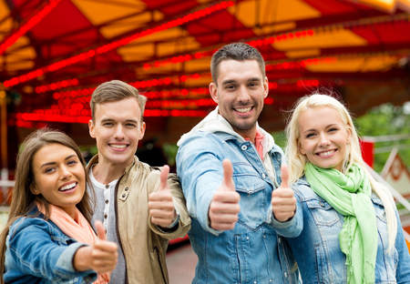 thumbs up group: leisure, amusement park and friendship concept - group of smiling friends showing thumbs up with carousel on the back