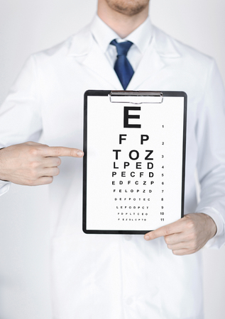 healthcare, medicine and vision concept - male ophthalmologist with eye chart photo