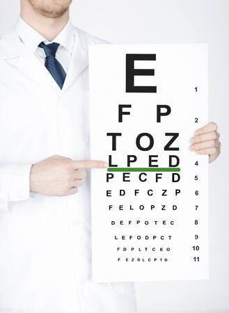 oculista: cuidado de la salud, la medicina y el concepto de la visión - Oftalmólogo de sexo masculino con la carta de ojo Foto de archivo
