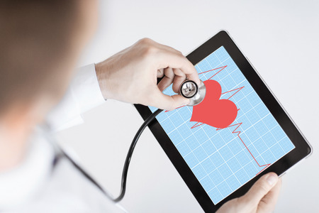 doctor with stethoscope listening heart beat on tablet pc photo