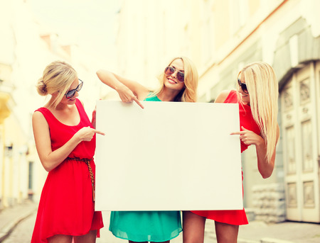 fancy dress party: summer holidays, , travel, tourism and advertisement concept - three happy blonde women with blank white board in the city