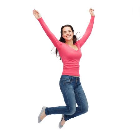 La felicità, la libertà, il movimento e le persone concetto - sorridente giovane donna che salta in aria Archivio Fotografico - 30614250