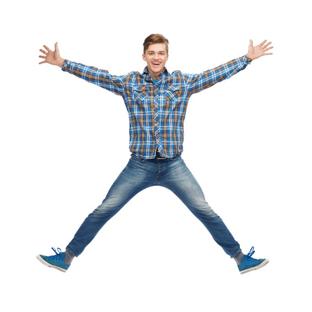 happiness, freedom, movement and people concept - smiling young man jumping in air photo