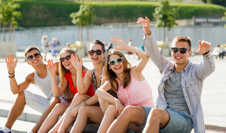 travelling: friendship, leisure, summer, gesture and people concept - group of laughing friends sitting on city square
